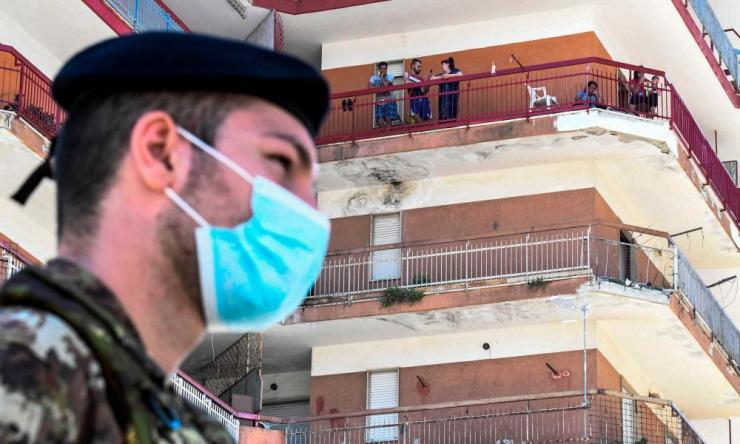An Italian soldier standing guard below buildings inside the red zone where 49 cases of coronavirus infections were confirmed in Mondragone, Southern Italy.