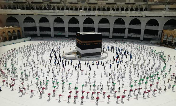 Hundreds of Muslim pilgrims circle the Kaaba in a socially distanced way.