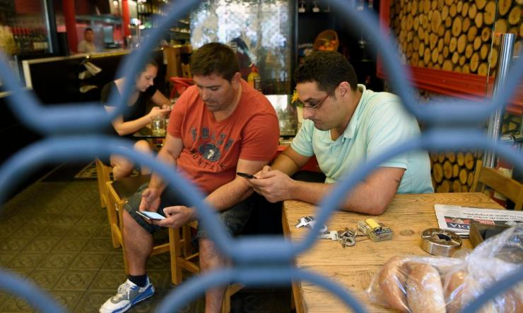 """People check their smartphones in a bar behind an iron curtain as they wait after a van ploughed into the crowd, killing 13 persons and injuring over 50 on the Rambla in Barcelona on August 17, 2017. A driver deliberately rammed a van into a crowd on Barcelona's most popular street on August 17, 2017 killing at least 13 people before fleeing to a nearby bar, police said. Officers in Spain's second-largest city said the ramming on Las Ramblas was a """"terrorist attack"""" and a police source said one suspect had left the scene and was """"holed up in a bar"""". The police source said they were hunting for a total of two suspects. / AFP PHOTO / LLUIS GENELLUIS GENE/AFP/Getty Images"""