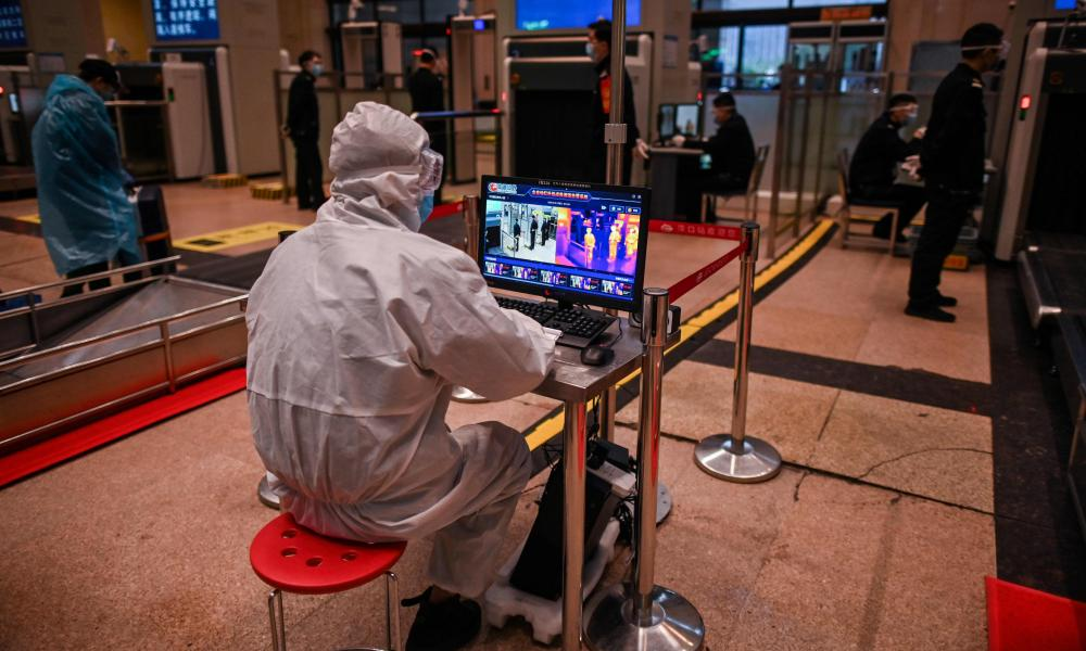 A worker wearing a protective suit waits to control the temperature of passengers at Hankou Railway Station in Wuhan, in China's central Hubei province early on 8 April 2020.