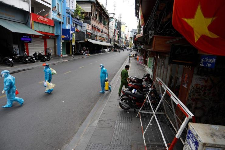 Medical workers collecting test samples from residents walk past in Ho Chi Minh City.