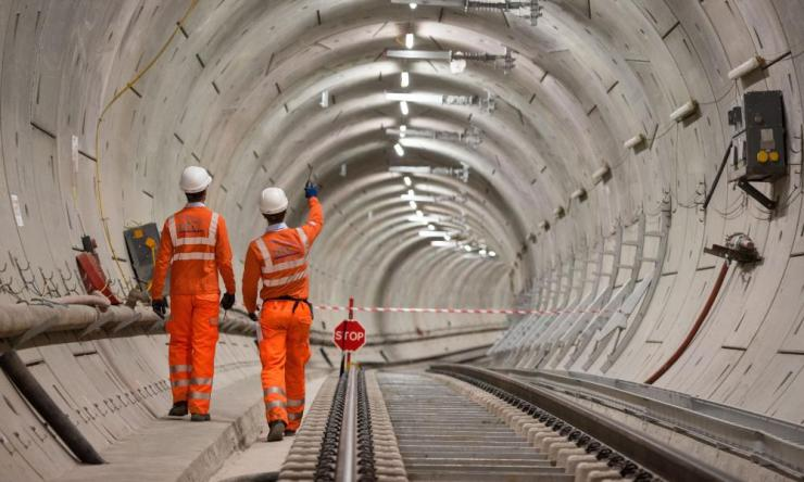 Crossrail engineers walk alongside tracks. The opening of London's new east-west railway has been delayed by nearly a year, to autumn 2019