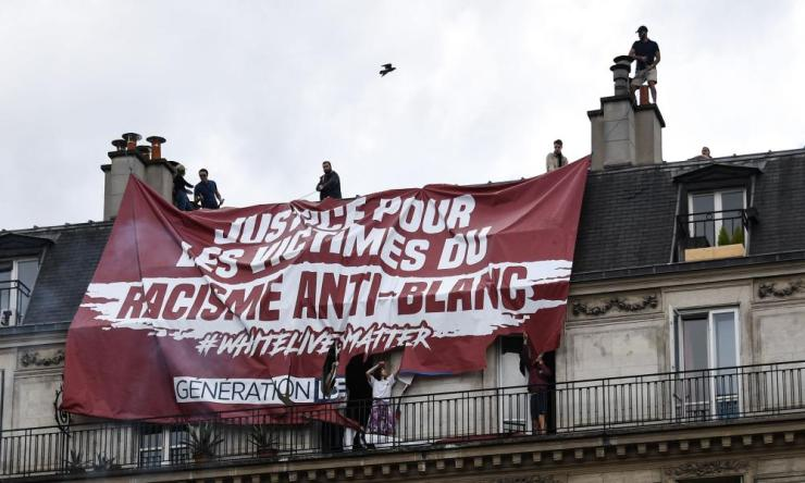 Residents try to remove a banner installed on the roof by members of far right group Generation Identitaire.