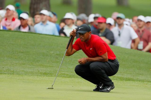 Woods lines up his putt on the 6th.