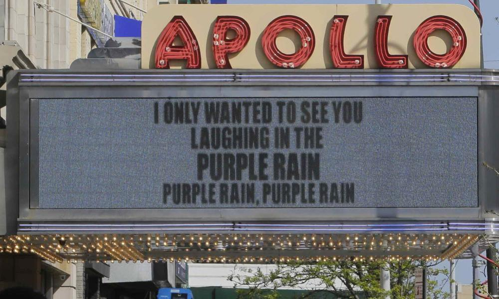 Pedestrians pass the Apollo Theater displaying lyrics from songs by Prince