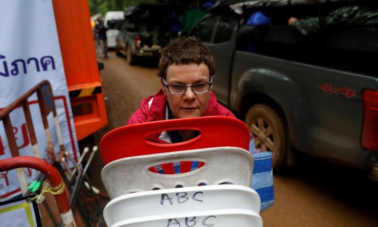 A journalist stacks up chairs up as she prepares to leave the site of Tham Luang cave complex
