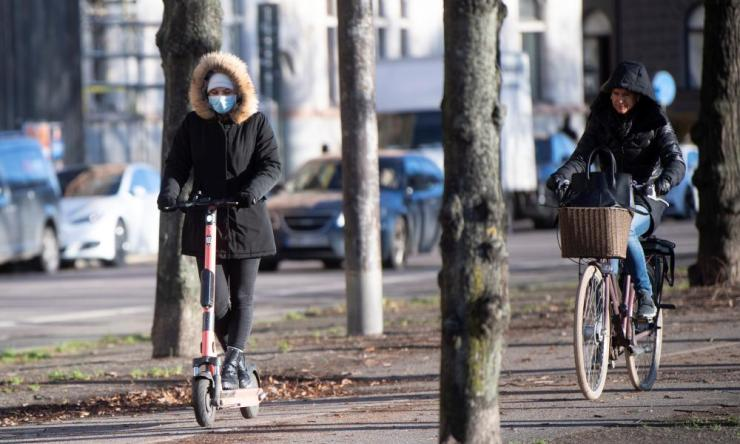 A woman rides an electric scooter wearing a protective mask, amid the continuous spread of the coronavirus pandemic, along Standvagen in Stockholm, Sweden, 20 November 2020.
