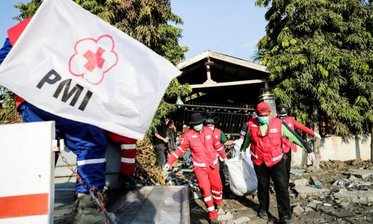 Members of the Indonesian Red Cross carry the body of a tsunami victim from a collapsed house at Talise beach in Palu, central Sulawesi, Indonesia