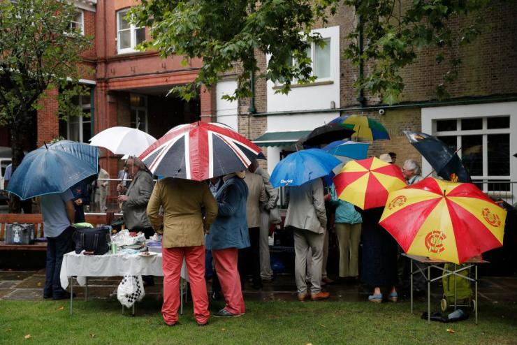Spectators shelter under umbrellas as they try to have lunch in the rain.