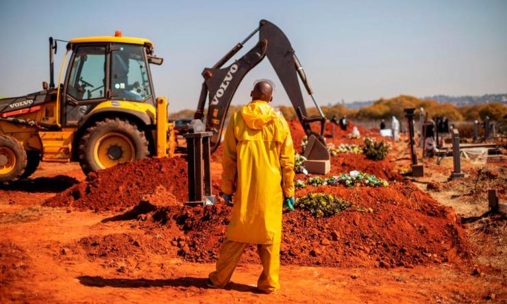 An undertaker wearing personal protective equipment watches as an excavator fills the grave of a Covid-19 victim at the Westpark cemetery in Johannesburg, on 22 July 2020.