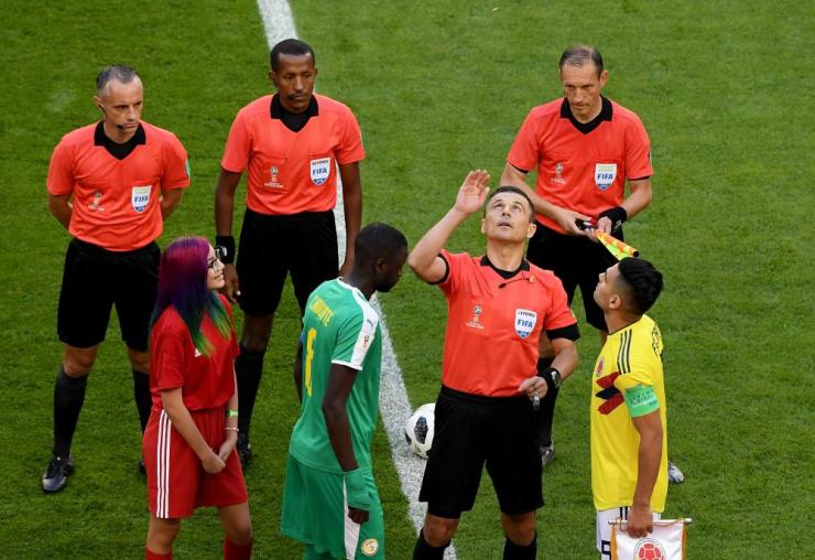 Referee Milorad Mazic performs the coin toss.
