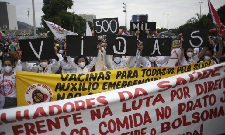 """Women hold up placards with a message that reads in Portuguese; """"500K deaths! His fault!"""" during a demonstration against Brazilian President Jair Bolsonaro's handling of the coronavirus pandemic and economic policies protesters say harm the interests of the poor and working class, in Rio de Janeiro, Brazil. Brazil is approaching an official COVID-19 death toll of 500,000 — second-highest in the world."""