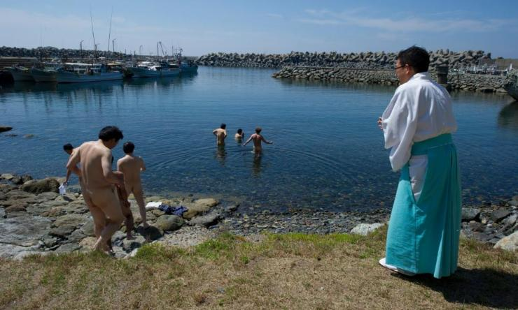 Shinto priest Sadoharu Nagatomo guides a group of men in a purification ritual before entering the island of Okinoshima.