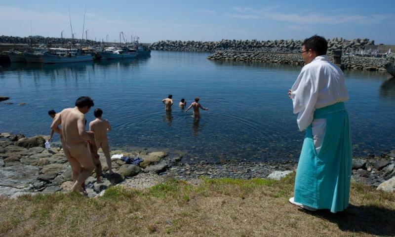 Shinto priest Sadoharu Nagatomo guides a group of men in a purification ritual before entering the island of Okinoshima.