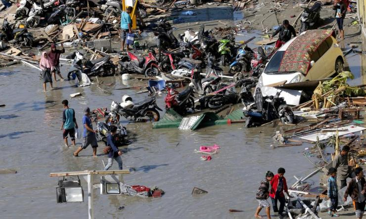 People survey the damage outside a flooded shopping mall in Palu