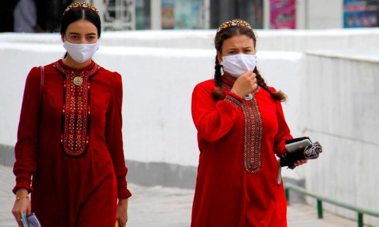 Turkmen women wearing face masks walk in Ashgabat on 13 July.