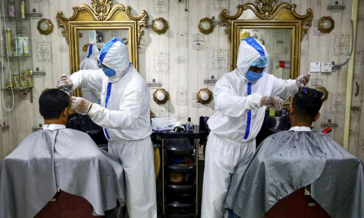 Barbers wearing protective suits and face masks cut hair at a salon in Dhaka, Bangladesh.