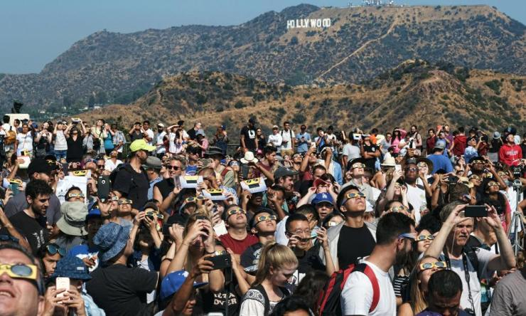 A crowd gathers in front of the Hollywood sign at the Griffith Observatory to watch the solar eclipse in Los Angeles.