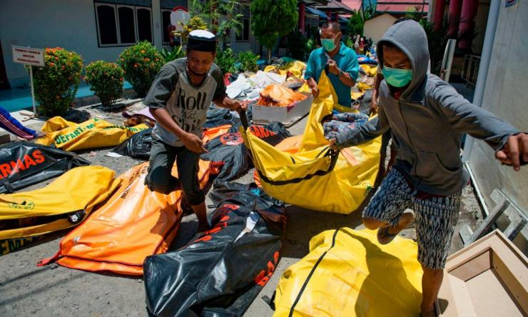 Family members carry the body of a relative to the compounds of a police hospital in Palu