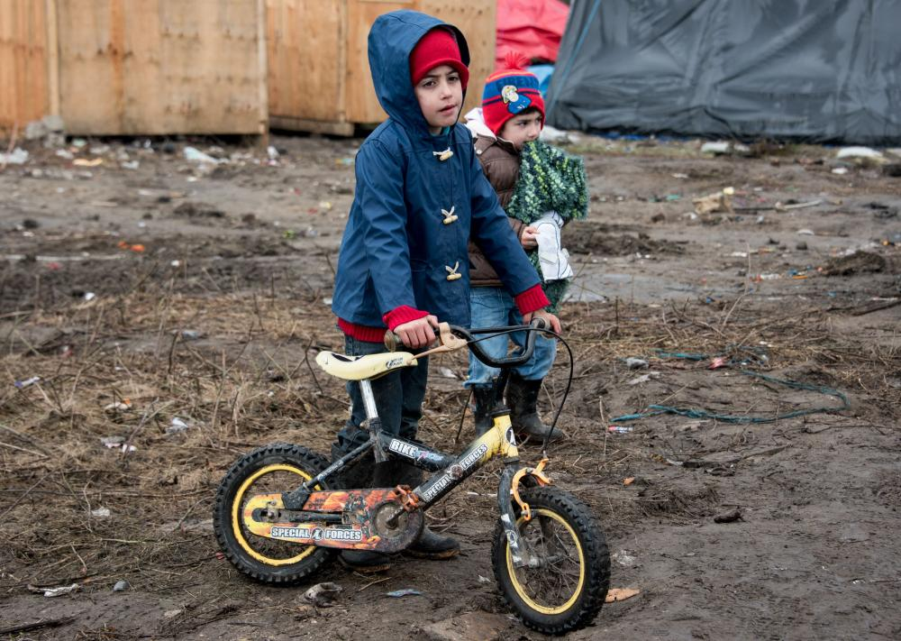 Migrant children play in the Calais camp