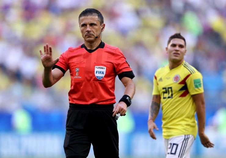Referee Milorad Mazic gestures after consulting VAR on the penalty incident.