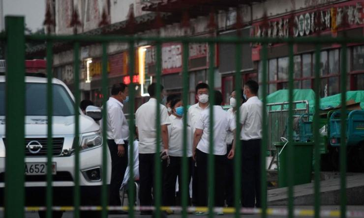 Officials gather outside the Xinfadi meat wholesale market in Beijing after it was closed for disinfection and environmental sample collection.