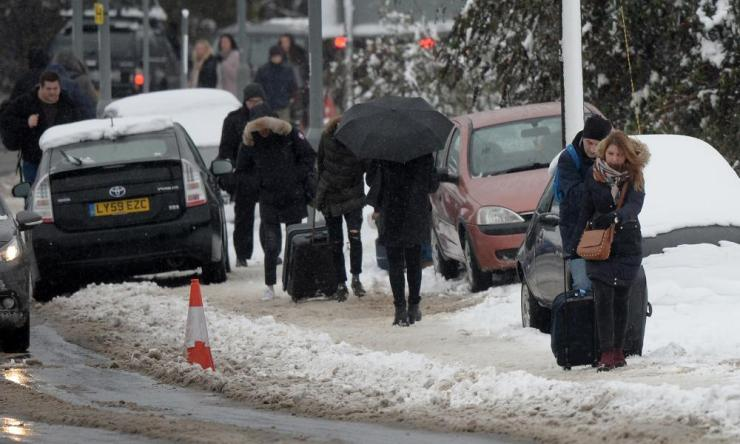 Passengers had to walk up the steep hill to Luton airport dragging their suitcases due to a lack of transport due to the weather