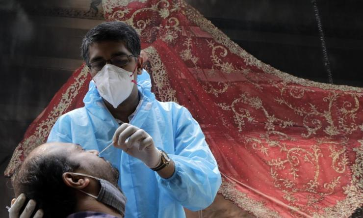 A health worker takes swab sample of a woman to test for Covid-19 outside a garment shop in Mumbai, India, Tuesday, 13 October 2020.