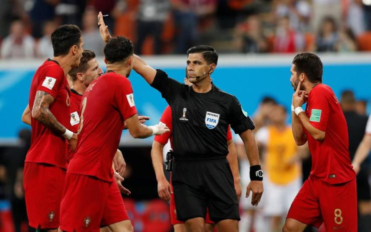 Referee Enrique Caceres is surrounded by Portugal players.