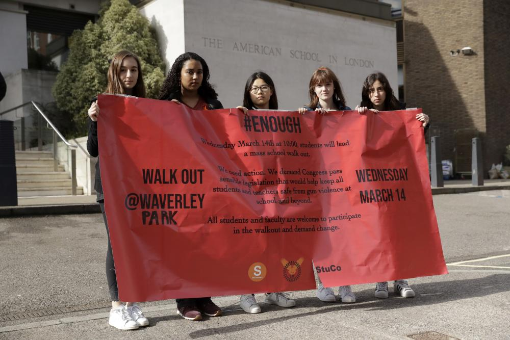 Students display a banner outside the American School in London after taking part in the walkout which was attended by approximately 300 others