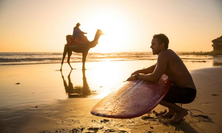 A surfer and a camel share the beach at Taghazout, Morocco.