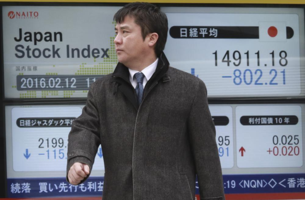 A man walks past an electronic stock board showing Japan's Nikkei 225 in Tokyo, Friday, Feb. 12, 2016. Asian shares fell Friday, with Japan's Nikkei 225 index tumbling more than 5 percent following a sell-off in European and U.S. markets. (AP Photo/Eugene Hoshiko)