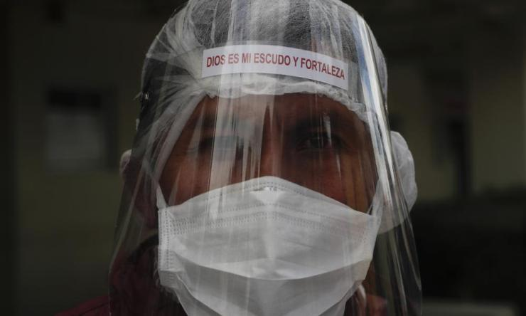 "A health worker in full protective gear and with a face shield with text that reads in Spanish ""God is my shield and my strength,"" attends an official act by local authorities as they hand over hospital beds to the Del Norte Hospital, which is treating COVID-19 patients exclusively, in El Alto, Bolivia."