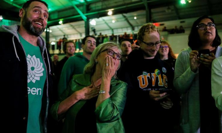 Green Party leader Elizabeth May and supporters react while observing the live federal election results, which predict the party will win three seats, an increase of one seat on their results from the last election.