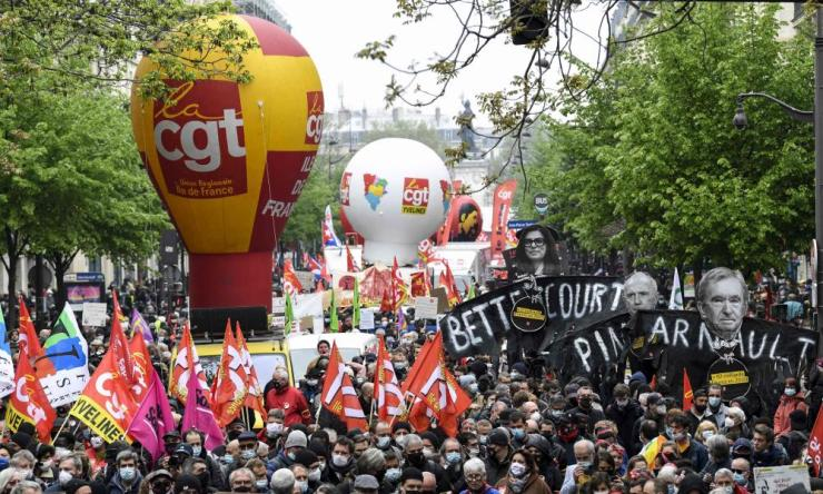 Protestors wave trade unions flags as they take part in the annual Labour Day workers' demonstration, in Paris on 1 May.