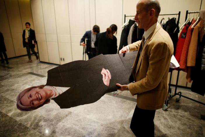 A man moves a cut-out of Hillary Clinton.