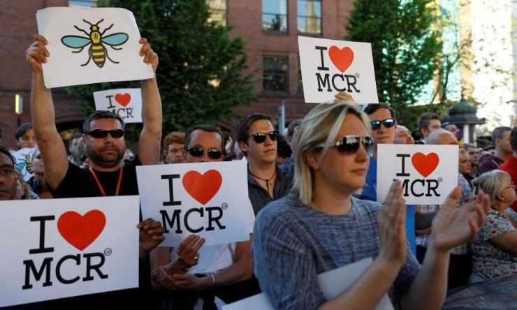 People hold placards as they take part in a vigil in Manchester's Albert Square.