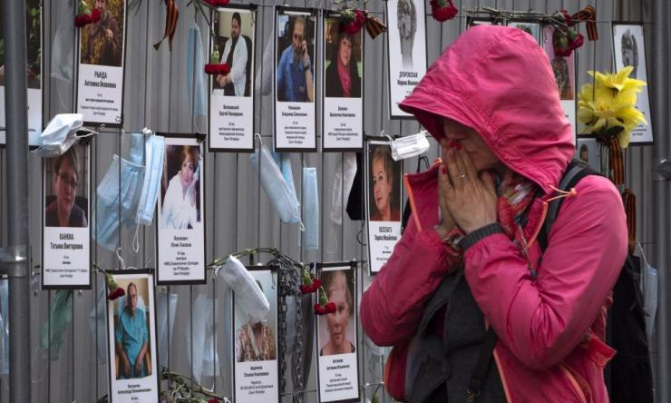 A woman reacts as she walks past portraits of St Petersburg medical workers in Russia who have died from coronavirus.