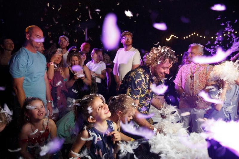 Young and old enjoy being feather-bombed at the end of the Place des Anges performance.