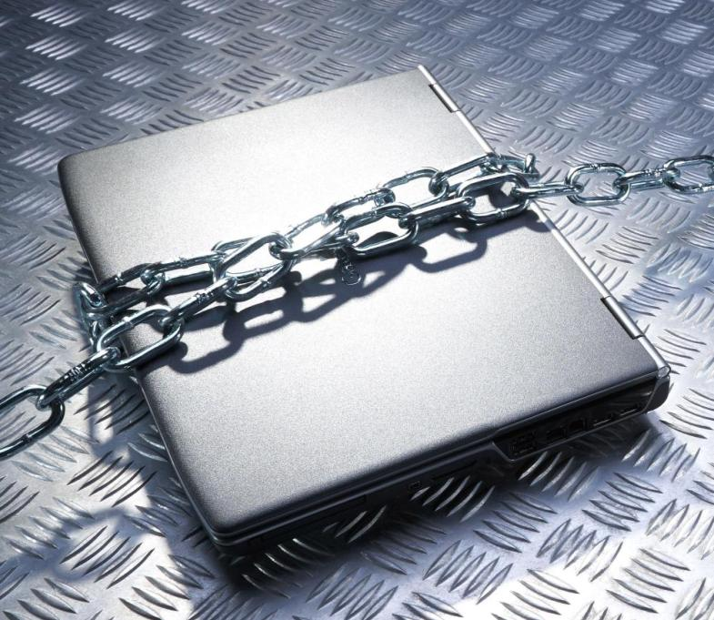 Laptop in chains on metal back ground. Image shot 2007. Exact date unknown.<br>BF89AB Laptop in chains on metal back ground. Image shot 2007. Exact date unknown.