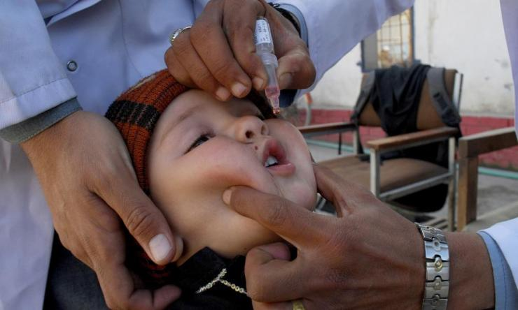 A health worker gives a polio vaccine to a child in Peshawar, Pakistan, in February, before the programme was suspended.