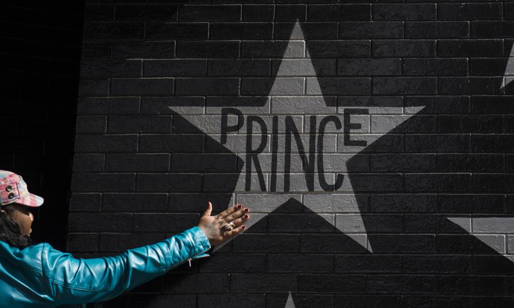 A woman touches the Prince star on the wall outside the First Avenue nightclub on April 21, 2016 in Minneapolis, Minnesota