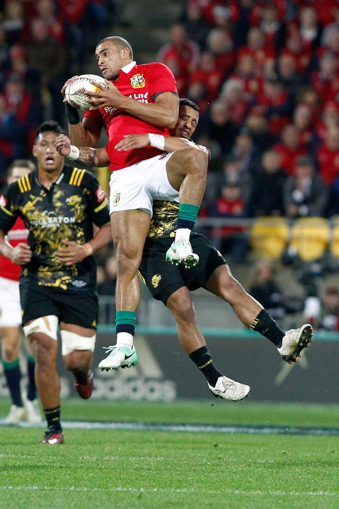 Jonathan Joseph of the Lions, left, is caught in the air by Te Toiroa Tahuriorangi of the Hurricanes.