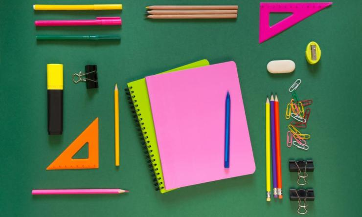 Colorful school supplies, pink book on green. Top view, flat lay, copy space