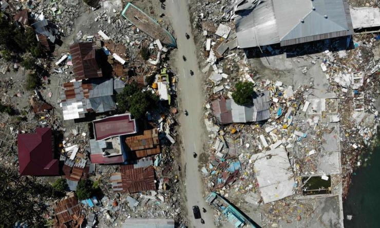 This aerial photo shows people driving past a washed up boat and collapsed buildings in Palu