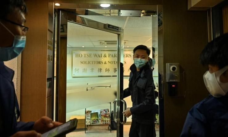 Police are seen inside the office of former pro-democracy lawmaker and lawyer Albert Ho after as many as 50 Hong Kong opposition figures were arrested
