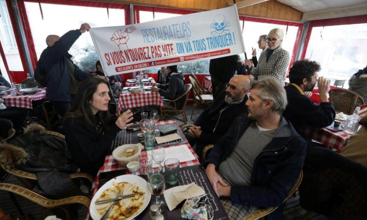 Customers enjoy lunch at Le Poppies in Nice, which owner Christophe Wilson has opened as an act of civil disobedience in protest against the government-ordered closure of bars and restaurants in France.