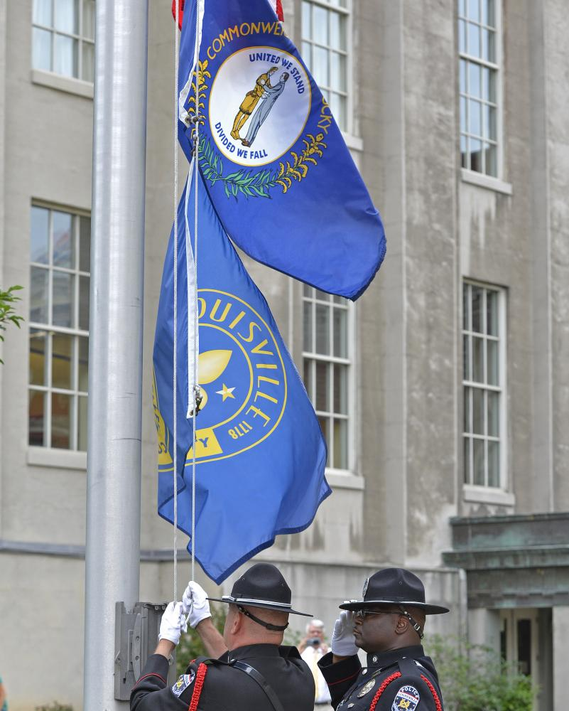 Members of the Louisville Metro Police Color Guard lower the flags at Louisville city hall.
