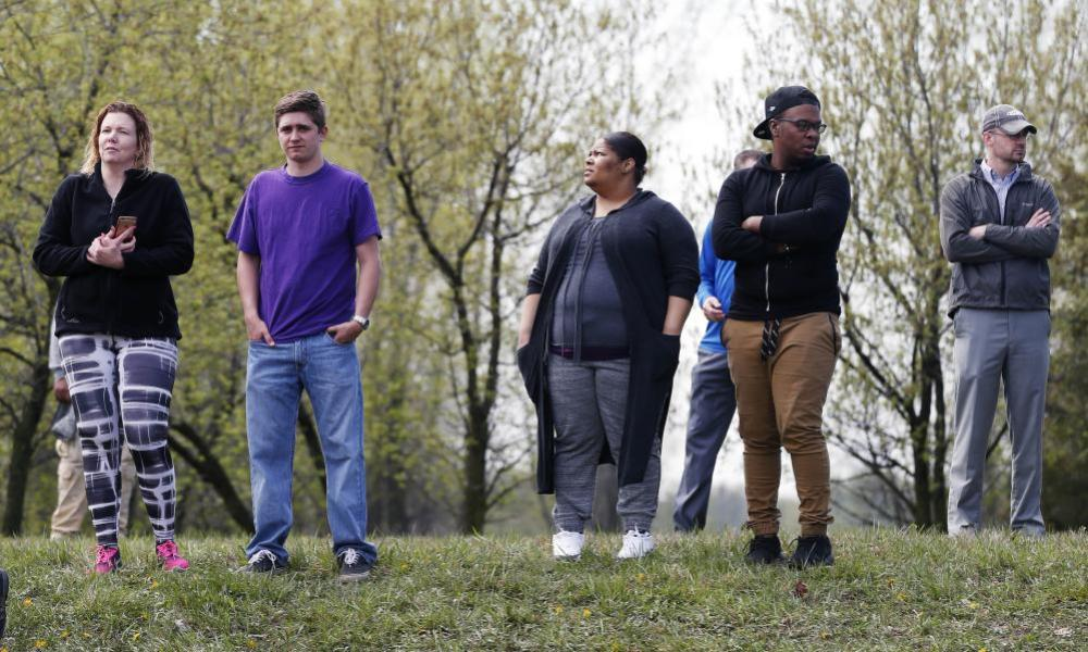 People watch on a slight hill across from Paisley Park Studios