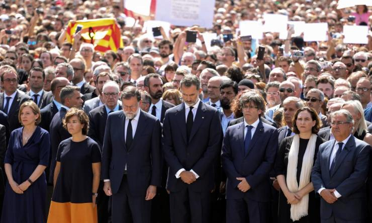 Spain's King Felipe looks down as he stands along politicians including Mariano Rajoy while they observe a minute of silence in Barcelona.